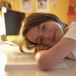 Girl (6-8) resting head on book, near a desk lamp.